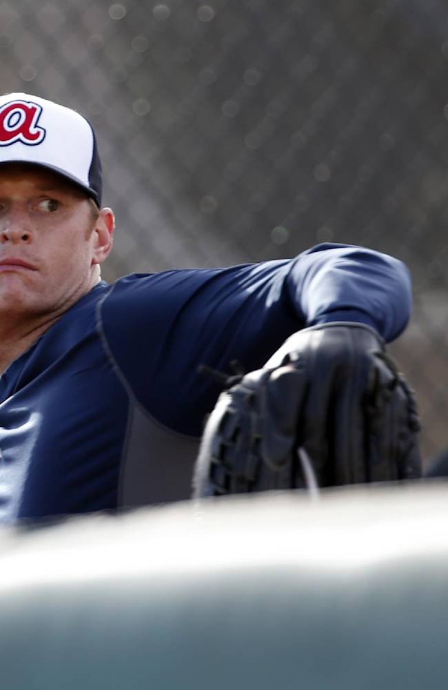 Atlanta Braves pitcher Gavin Floyd throws as manager Fredi Gonzalez, right, watches during a spring training baseball workout, Thursday, Feb. 13, 2014, in Kissimmee, Fla