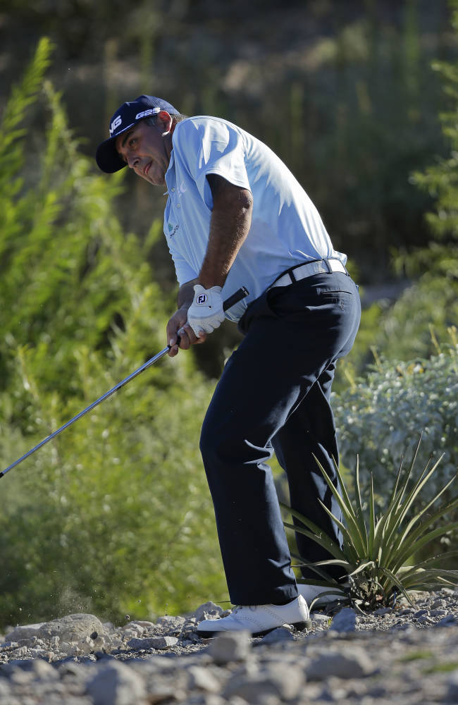 Angel Cabrera, of Argentina, follows through after hitting out of the rocks onto the 15th green in the first round of the Shriners Hospitals for Children Open golf tournament, Thursday, Oct. 17, 2013, in Las Vegas