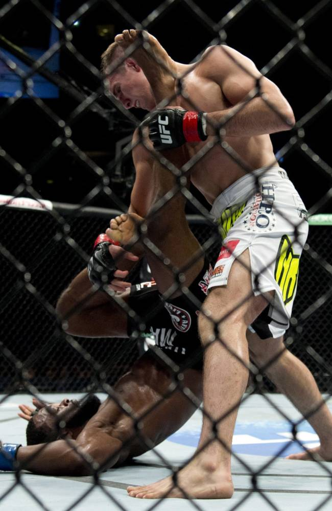 Rory MacDonald, of Canada, pins Tyron Woodley, of the United States, to the mat during the welterweight bout at UFC 174 in Vancouver, British Columbia, Saturday, June, 14, 2014