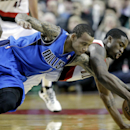 Dallas Mavericks guard Monta Ellis, left, and Portland Trail Blazers guard Wesley Matthews dive for a loose ball during the second half of an NBA basketball game in Portland, Ore., Saturday, Dec. 7, 2013. Ellis scored 22 points, including a game winning