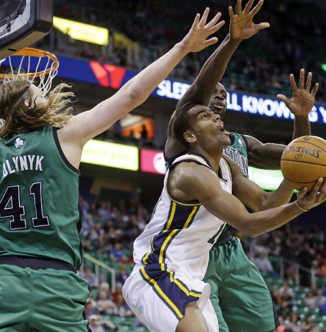 Utah Jazz's Alec Burks, right, shoots as Boston Celtics' Kelly Olynyk (41) and teammate Brandon Bass, rear, defend in the second half of an NBA basketball game, Monday, Feb. 24, 2014, in Salt Lake City. The Jazz won 110-98