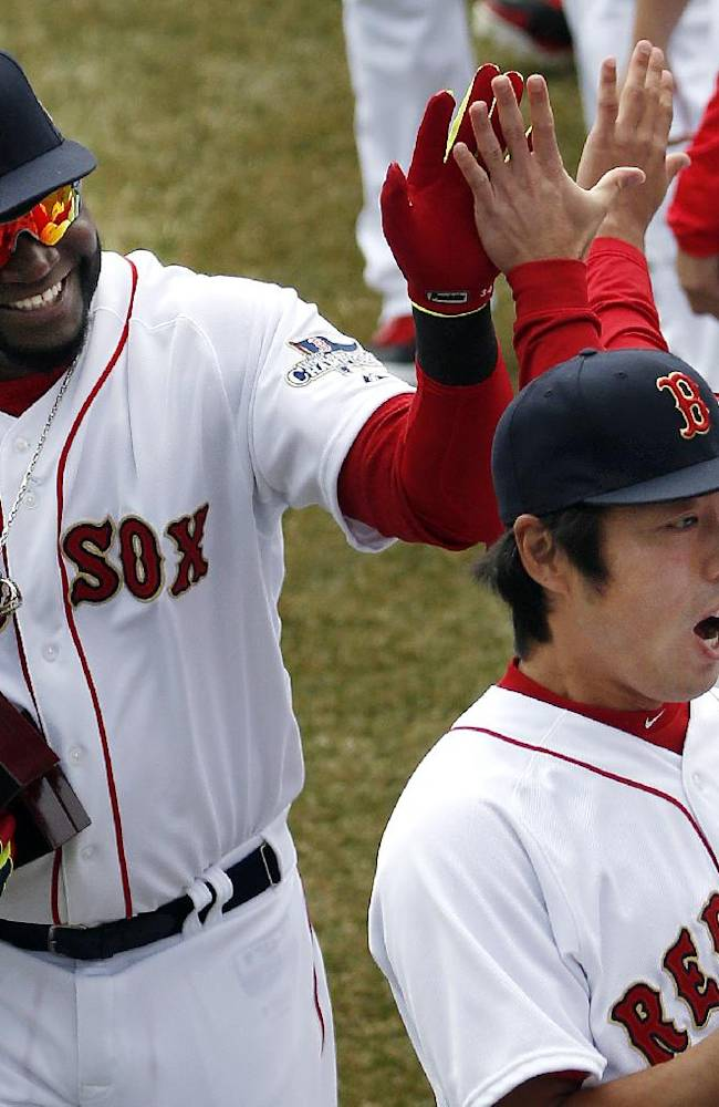 Boston Red Sox designated hitter David Ortiz, left, and relief pitcher Koji Uehara, lower right, celebrate with teammates after receiving their 2013 World Series rings at Fenway Park in Boston, Friday, April 4, 2014, during home opening day ceremonies prior to a baseball game between the Boston Red Sox and the Milwaukee Brewers
