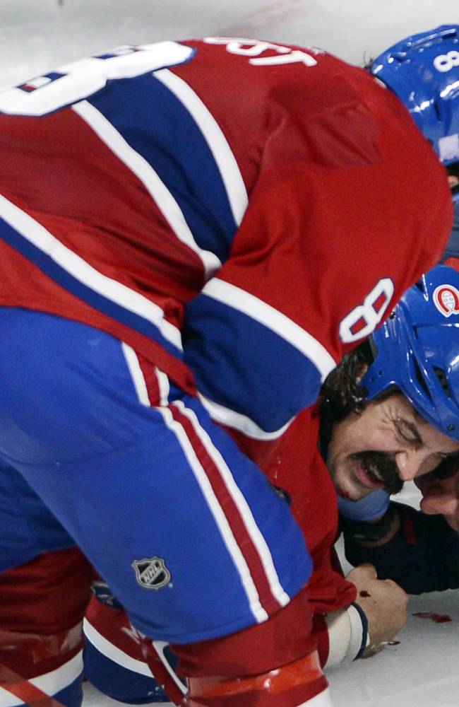 In this Oct. 1, 2013 photo, Montreal Canadiens winger George Parros (15) is treated by medical staff as teammate Brandon Prust looks on after he hit his head on the ice during a fight with Toronto Maple Leafs right wing Colton Orr during third period NHL action in Montreal. Parros sustained a concussion