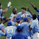 Kansas City Royals' Mike Moustakas, center, celebrates with teammates after hitting a solo home run to win a baseball game during the 13th inning against the Seattle Mariners, Thursday, Sept. 5, 2013, in Kansas City, Mo. The Royals won the game 7-6. (AP Photo/Charlie Riedel)