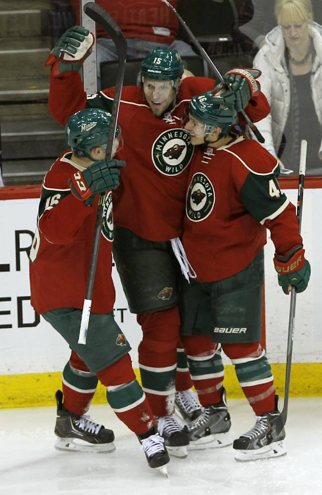 Minnesota Wild left wing Jason Zucker, left, and defenseman Jared Spurgeon, right, congratulate left wing Dany Heatley, center, after his goal on Tampa Bay Lightning goalie Ben Bishop during the third period of an NHL hockey game in St. Paul, Minn., Tuesday, Feb. 4, 2014. The Wild won 2-1