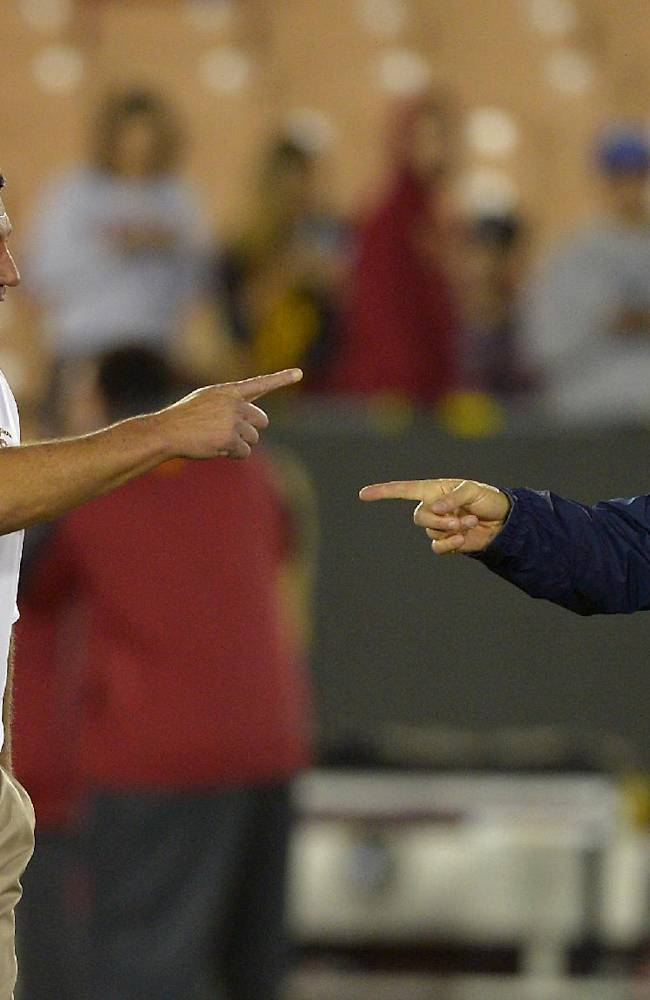 Southern California interim coach Ed Orgeron, left, talks with Arizona coach Rich Rodriguez prior to an NCAA college football game, Thursday, Oct. 10, 2013, in Los Angeles