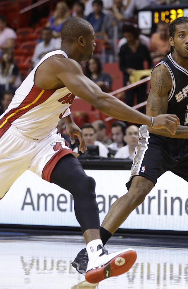 San Antonio Spurs' Kawhi Leonard (2) drives to the basket as Miami Heat's Dwyane Wade, left, defends during the first half of an NBA preseason basketball game, Saturday, Oct. 19, 2013, in Miami