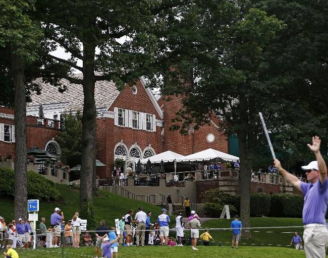 A marshall asks for quiet as a group tees off in front of the clubhouse at Fox Chapel Golf Club in Pittsburgh, during the first round of the Senior Players Championship golf tournament, Thursday, June 26, 2014