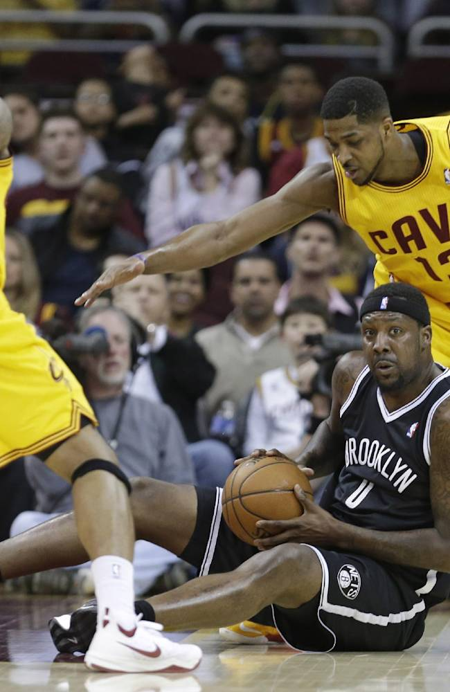 Cleveland Cavaliers' Alonzo Gee (33) and Tristan Thompson (13) loom over Brooklyn Nets' Andray Blatche (0) during the first quarter of an NBA basketball game Wednesday, April 16, 2014, in Cleveland