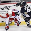 Pittsburgh Penguins' Simon Despres (47) collides with Washington Capitals' Michael Latta (46) during the first period of an NHL hockey game in Pittsburgh Saturday, Dec. 27, 2014. (AP Photo/Gene J. Puskar)