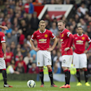 Manchester United players including captain Wayne Rooney, centre right, wait for play to resume after Swansea City's second goal during their English Premier League soccer match at Old Trafford Stadium, Manchester, England, Saturday, Aug. 16, 2014