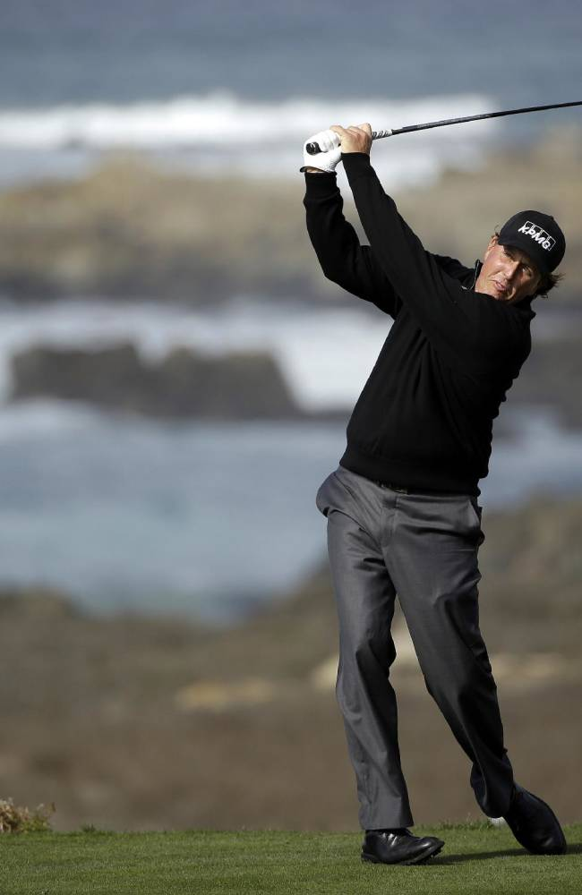 Phil Mickelson follows his drive from the 13th tee of the Shore Course at Monterey Peninsula during the first round of the AT&T Pebble Beach Pro-Am golf tournament Thursday, Feb. 6, 2014, in Pebble Beach, Calif