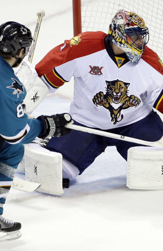 Florida Panthers goalie Roberto Luongo, right, stops a shot next to San Jose Sharks' Joe Pavelski (8) during the third period of an NHL hockey game on Tuesday, March 18, 2014, in San Jose, Calif. Florida won 3-2