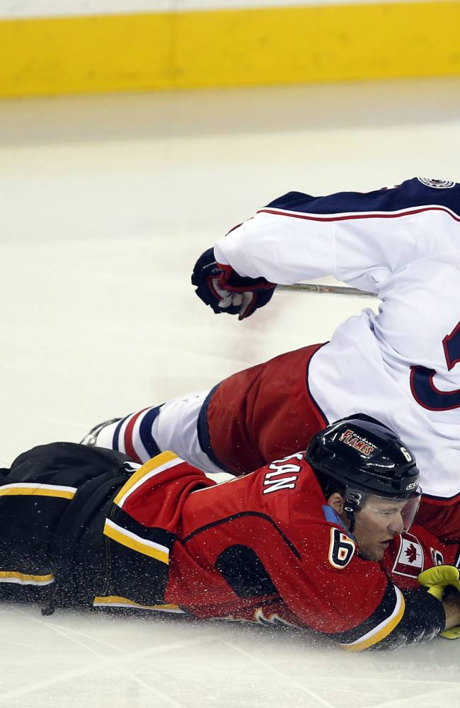 Columbus Blue Jackets' Jack Skille (5) crashes down on Calgary Flames' Dennis Wideman during first period NHL hockey action in Calgary, Alberta, Wednesday, Nov. 20, 2013