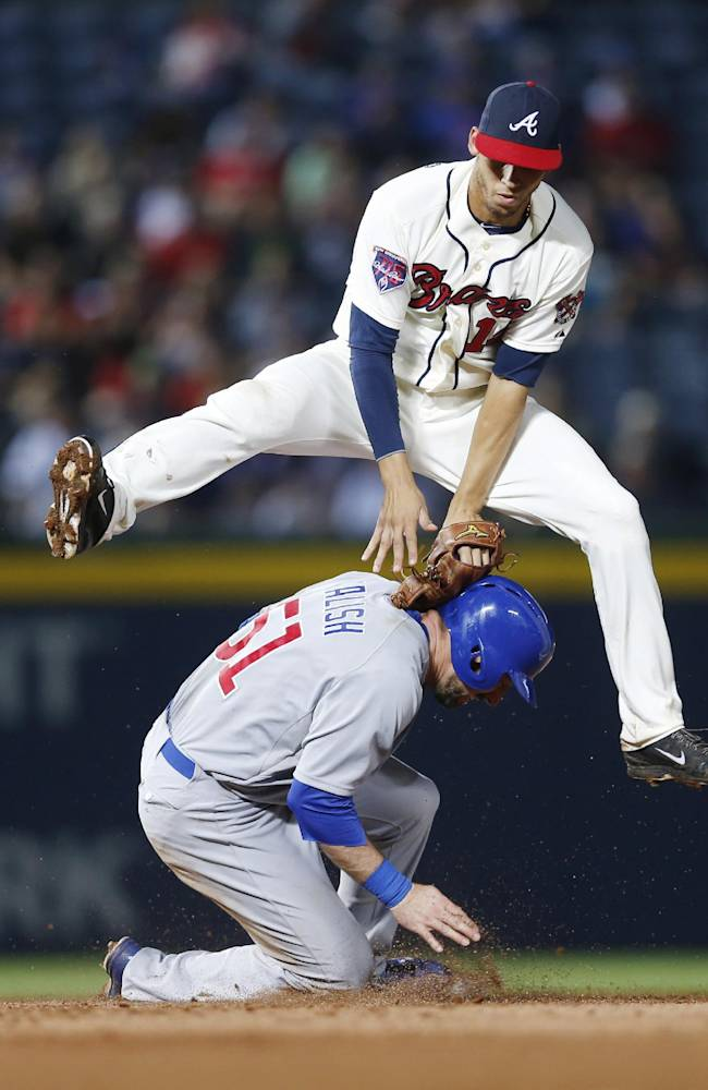 Atlanta Braves shortstop Andrelton Simmons (19) clears Chicago Cubs' Ryan Kalish (51) as he turns a double play on an Anthony Rizzo ground ball in the sixth inning of a baseball game, Saturday, May 10, 2014, in Atlanta