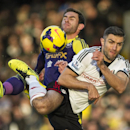 Fulham s Aaron Hughes, right, fights for the ball with Swansea City s Angel Rangel, during their English Premier League soccer match, at the Craven Cottage stadium in London, Saturday, Nov. 23, 2013