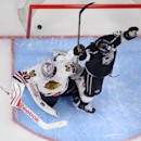 Chicago Blackhawks goalie Corey Crawford, left, is scored on by Los Angeles Kings defenseman Jake Muzzin, not seen, as right wing Dustin Brown celebrates during the third period of an NHL hockey game, Wednesday, Jan. 28, 2015, in Los Angeles. The Kings w