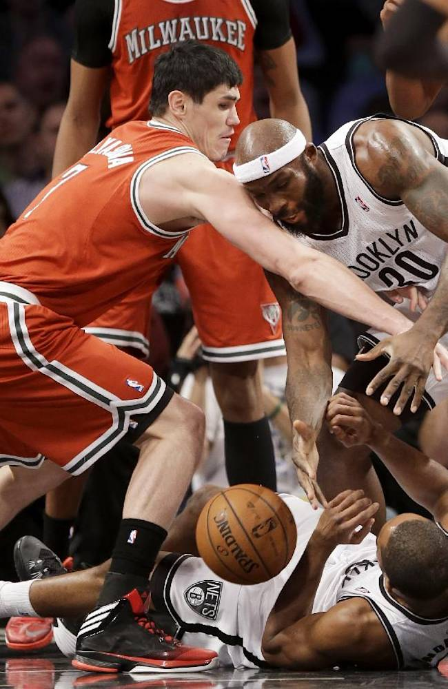 Milwaukee Bucks' Ersan Ilyasova, left, fights for a rebound with Brooklyn Nets' Reggie Evans, right, and Alan Anderson, bottom, during the first half of an NBA basketball game at the Barclays Center, Friday, Dec. 27, 2013, in New York