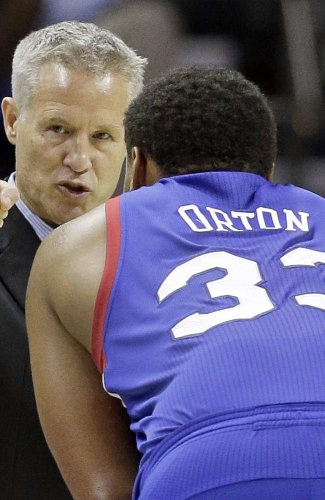Philadelphia 76ers head coach Brett Brown, back, talks with Daniel Orton, front, during the second half of a preseason NBA basketball game against the Charlotte Bobcats in Charlotte, N.C., Thursday, Oct. 17, 2013. The Bobcats won 110-84
