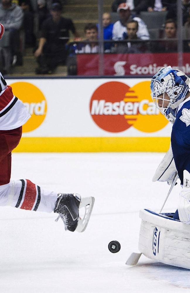 Toronto Maple Leafs goalie Jonathan Bernier, right, makes a save on a tip from Carolina Hurricanes forward Tuomo Ruutu, left, during the first period of an NHL hockey game in Toronto on Thursday, Oct. 17, 2013