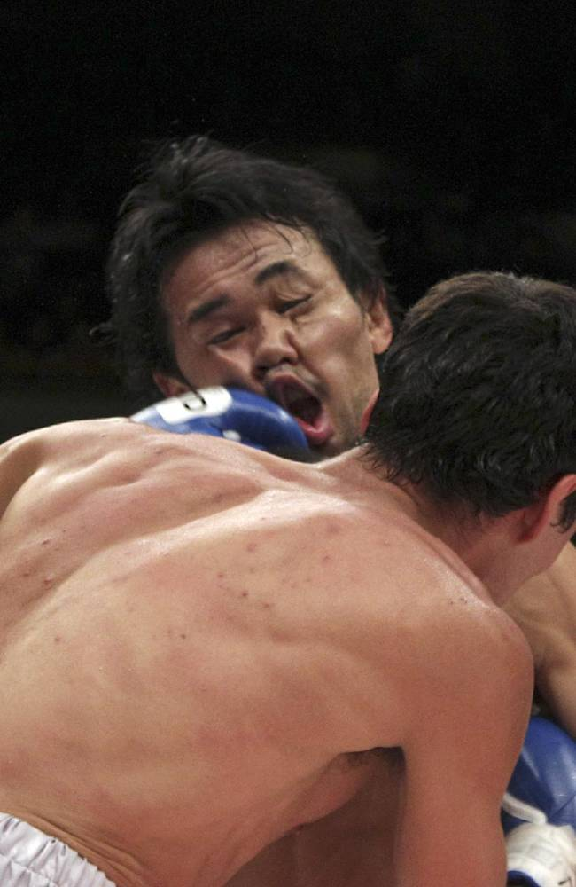 Japanese champion Shinsuke Yamanaka, back, gets a punch from Mexican challenger Alberto Guevara in the third round of their WBC bantamweight title bout in Tokyo, Sunday, Nov. 10, 2013. Yamanaka knocked out Guevara in the ninth round to defend his title