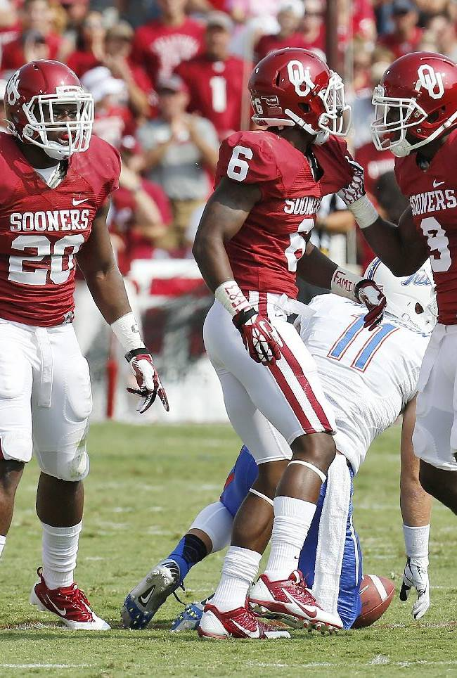 Oklahoma defensive back Gabe Lynn (9) and defensive back Stanvon Taylor (6) celebrate Taylor's tackle of Tulsa's Derek Patterson (11) as linebacker Frank Shannon (20) looks on in the first quarter of an NCAA college football game in Norman, Okla., Saturday, Sept. 14, 2013