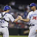 Los Angeles Dodgers' Kenley Jansen (74) shakes hands with catcher Drew Butera (31) after pitching the ninth inning in the Dodgers' 8-5 victory over the Arizona Diamondbacks during a baseball game Saturday, April 12, 2014, in Phoenix The Associated Press