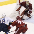 St. Louis Blues' Jori Lehtera (12), of Finland, scores a goal against Arizona Coyotes' Mike Smith, rear, as Coyotes' Oliver Ekman-Larsson (23), of Sweden, defends during the third period of an NHL hockey game Saturday, Oct. 18, 2014, in Glendale, Ariz. T