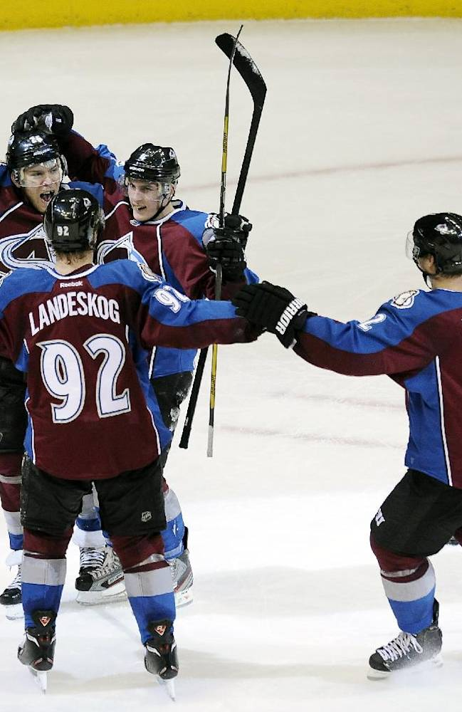 Colorado Avalanche center Paul Stastny, left, Avalanche left wing Gabriel Landeskog, bottom center, of Sweden, and Avalanche defenseman Tyson Barrie, center right, and Avalanche defenseman Nick Holden, right, celebrate Barrie's game-winning goal in overtime of an NHL hockey game against the Ottawa Senators on Wednesday, Jan. 8, 2014, in Denver. The Avalanche won 4-3