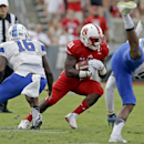 North Carolina State's Matt Dayes (21) runs the ball as Presbyterian's Isaiah Lynn (16) and Cory White, right, defend during the first half of an NCAA college football game in Raleigh, N.C., Saturday, Sept. 20, 2014 The Associated Press