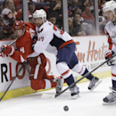 Washington Capitals defenseman John Carlson (74) takes control of the puck as Detroit Red Wings left wing Justin Abdelkader (8) is checked by Washington Capitals defenseman Karl Alzner (27) during the second period of an NHL hockey game in Detroit, Friday