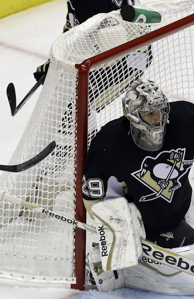 Pittsburgh Penguins goalie Marc-Andre Fleury (29) gloves the puck before Colorado Avalanche's P.A. Parenteau (15) and Jamie McGinn (11) can get a stick on it in the first period of an NHL hockey game in Pittsburgh Monday, Oct. 21, 2013