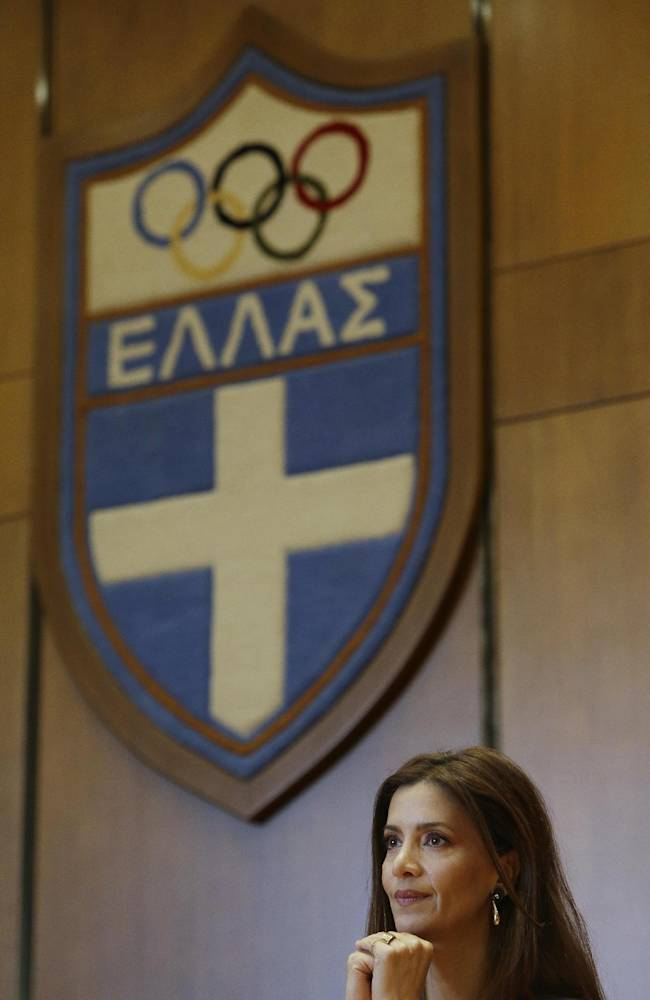 Greek actress Katerina Lehou attends a news conference as the logo of Greece's Olympic Committee is seen in the background in Athens, Monday, April 28, 2014. Lehou will be the new high priestess for the next four years. Her first appearance will be on Wednesday at the official lighting and hand over ceremony of the flame that will burn at the Aug. 16-28 Nanjing 2014 Youth Olympic Games in China