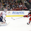 Washington Capitals goalie Braden Holtby, left, blocks a shot by New Jersey Devils center Adam Henrique during the second period of an NHL hockey game, Saturday, Dec. 6, 2014, in Newark, N.J The Associated Press