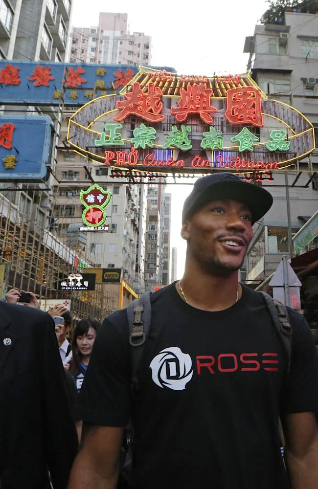 NBA star Derrick Rose of Chicago Bulls, center, walks in a shopping district in Hong Kong after attending a promotional event as part of his Asia tour Friday, Sept. 13, 2013. Rose will visit Manila, the Philippines, after touring Hong Kong