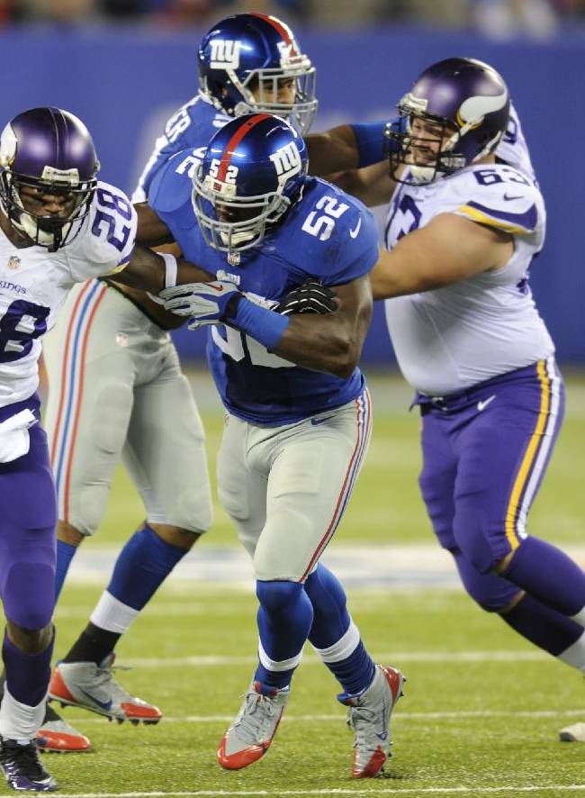 Minnesota Vikings running back Adrian Peterson (28) breaks a tackle by New York Giants' Jon Beason (52) as Jerome Felton (42) trails the play during the second half of an NFL football game Monday, Oct. 21, 2013 in East Rutherford, N.J