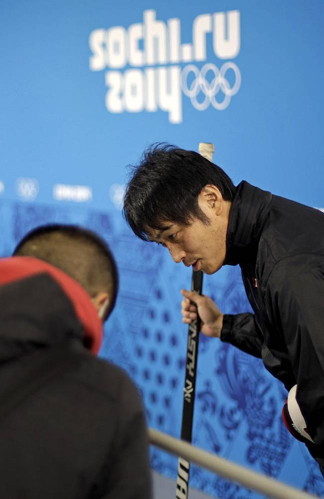 Head coach of the Japan women's ice hockey team Yuji Iizuka, right, bows to reporters after finishing an interview following a team practice at the 2014 Winter Olympics, Sunday, Feb. 2, 2014, in Sochi, Russia