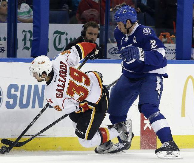 Tampa Bay Lightning defenseman Eric Brewer (2) trips Calgary Flames left wing T.J. Galiardi (39) during the third period of an NHL hockey game on Thursday, April 3, 2014, in Tampa, Fla. The Flames won the game 4-1