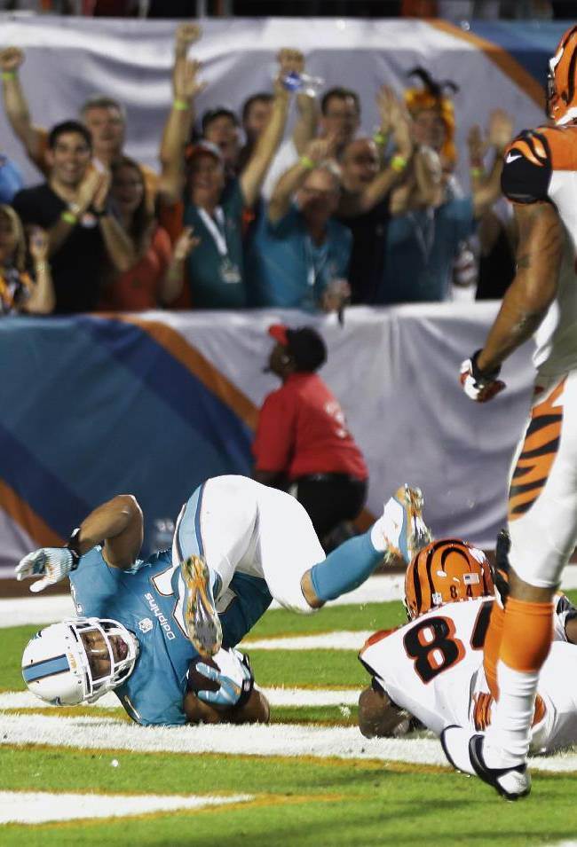 Miami Dolphins cornerback Brent Grimes scores a touchdown after Cincinnati Bengals quarterback Andy Dalton fumbled the ball during the second half of an NFL football game, Thursday, Oct. 31, 2013, in Miami Gardens, Fla. Bengals wide receiver Marvin Jones (82) and tight end Jermaine Gresham (84) are at right