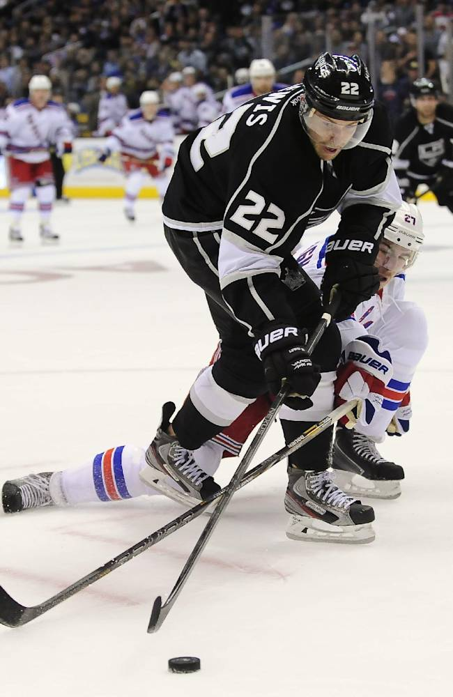 Los Angeles Kings center Trevor Lewis (22) and New York Rangers defenseman Ryan McDonagh reach for the puck during the second period of an NHL hockey game, Monday, Oct. 7, 2013, in Los Angeles