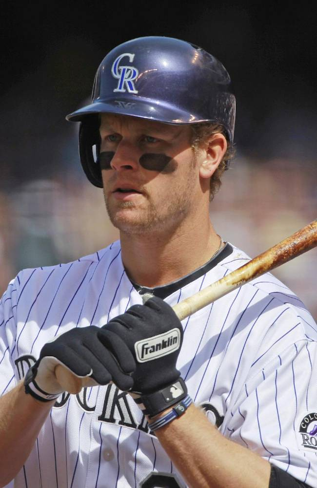 In this April 4, 2014 file photo, Colorado Rockies first baseman Justin Morneau waits in the on-deck circle to bat against the Arizona Diamondbacks in the first inning of a baseball game in Denver. Morneau is off to a solid start as he steps in for Todd Helton, who retired last year after 17 seasons. Morneau is hitting .387 and scooping up virtually everything in his vicinity at first base _ just like Helton used to do