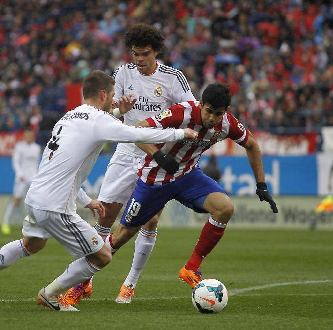 Atletico's Diego Costa, right, in action with Real's Sergio Ramos, left, during a Spanish La Liga soccer match between Atletico de Madrid and Real Madrid at the Vicente Calderon stadium in Madrid, Spain, Sunday, March 2, 2014