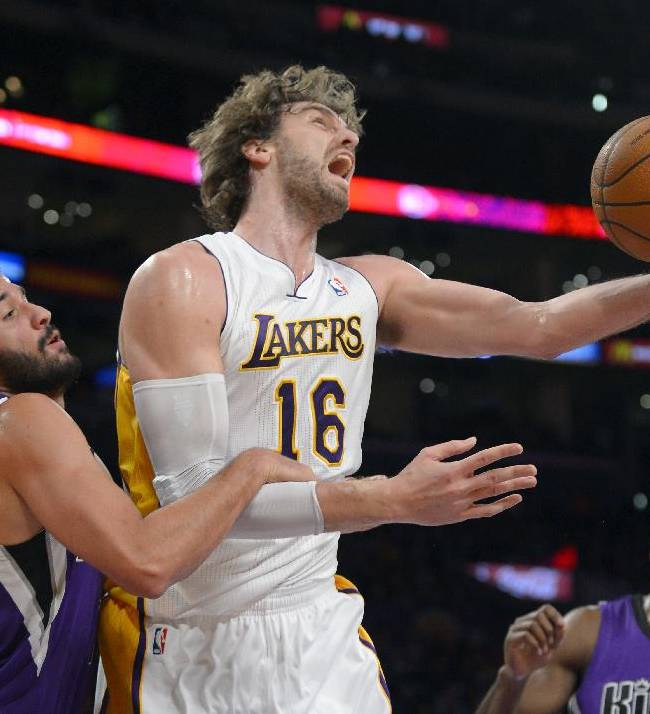 Los Angeles Lakers center Pau Gasol, right, of Spain, puts up a shot as Sacramento Kings guard Greivis Vasquez, of Venezuela, defends during the first half of an NBA basketball game Sunday, Nov. 24, 2013, in Los Angeles