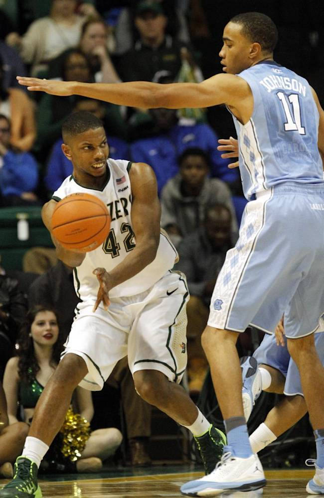 UAB forward Rod Rucker (42) passes the ball as he is pressured by North Carolina forward Brice Johnson (11) during the second half of an NCAA college basketball game on Sunday, Dec. 1, 2013, in Birmingham, Ala. UAB defeated North Carolina 63-59