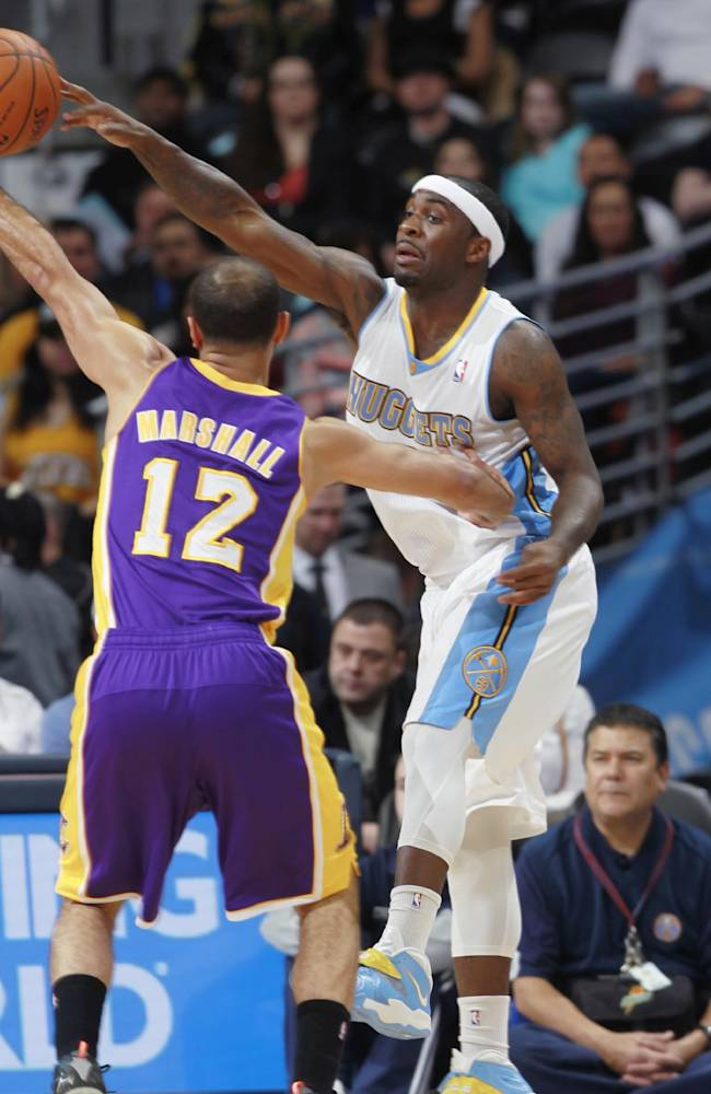 Denver Nuggets guard Ty Lawson, right, passes ball over Los Angeles Lakers guard Kendall Marshall in the first quarter of an NBA basketball game in Denver on Friday, March 7, 2014
