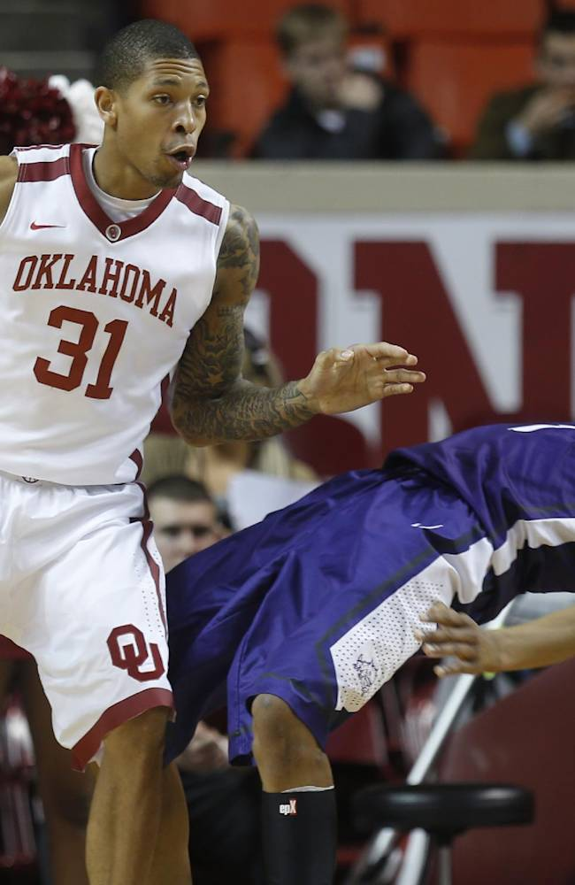 TCU center Karviar Shepherd (1) falls backward after being fouled by Oklahoma forward D.J. Bennett (31) during the first half of an NCAA college basketball game in Norman, Okla., Wednesday, Jan. 22, 2014. Oklahoma won 77-69