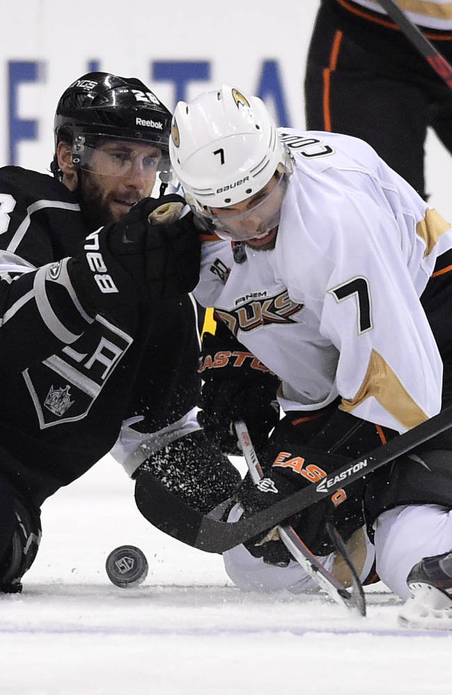 Los Angeles Kings center Jarret Stoll, left, and Anaheim Ducks center Andrew Cogliano battle for the puck during the third period in Game 4 of an NHL hockey second-round Stanley Cup playoff series, Saturday, May 10, 2014, in Los Angeles. The Duck won 2-0