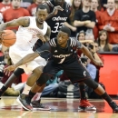 Louisville's Russ Smith, left, avoids the attempted steal by Cincinnati's Cashmere Wright during the first half of an NCAA college basketball game Monday, March 4, 2013 in Louisville, Ky. (AP Photo/Timothy D. Easley)