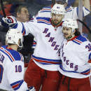 New York Rangers' Rick Nash, center, celebrates his goal with teammates J.T. Miller, left, and Mats Zuccarello, from Norway, during the first period of an NHL hockey game against the Calgary Flames in Calgary, Alberta, Tuesday, Dec. 16, 2014. (AP Photo/The Canadian Press, Jeff McIntosh)