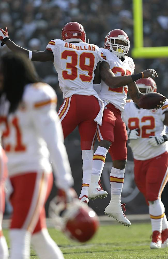 Kansas City Chiefs strong safety Eric Berry, top right, celebrates with defensive back Husain Abdullah (39) after returning an interception by Oakland Raiders quarterback Matt McGloin for a 47-yard touchdown during the first quarter of an NFL football game in Oakland, Calif., Sunday, Dec. 15, 2013